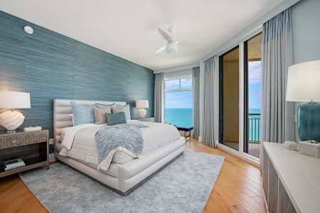 a beach-style guest bedroom with the cerulean teal and gray wall