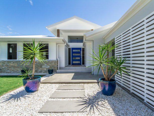 a coastal concrete floor entryway idea with a passionate blue dulux front door