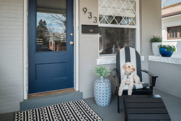 a small eclectic front porch with a pretty dark sherwin williams naval blue door