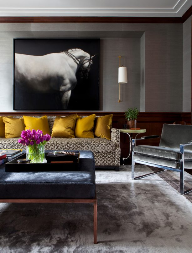 cozy living room with gray silk rug and gold plush pillows