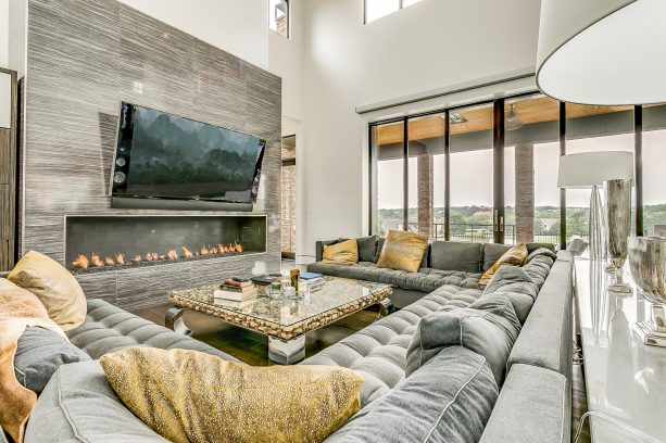 trendy living room with a huge sectional gray sofa and gold throw pillows