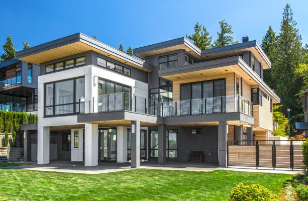 large trendy house featuring a metal roof and gray siding color combination