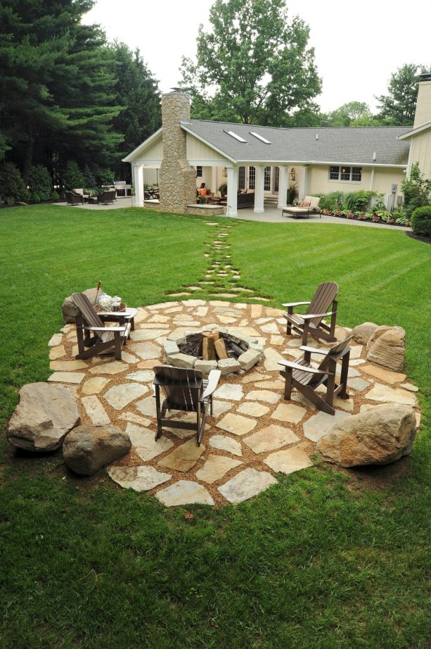 a huge timeless backyard with limestone flagstone paver patio and a fire pit