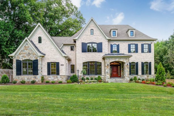 beige three-story brick house featuring glossy shutters