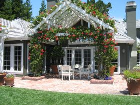 bright attached pergola with flowers to a roof of a gray house